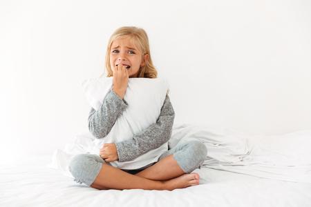 ベッドに座って午前中にカメラを見ながら枕を抱きしめた、怯えた少女の肖像画 写真素材