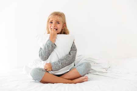 Retrato de una niña asustada que abraza la almohada mientras que se sienta en cama y mira la cámara por la mañana Foto de archivo