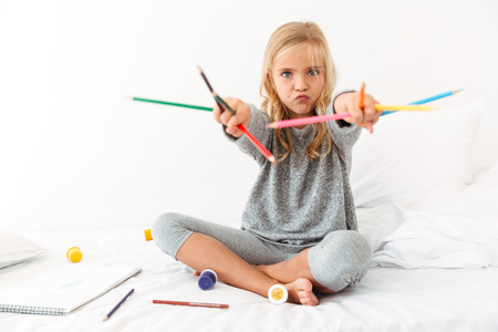Funny little girl in gray pajamas playing with colorful pencils, looking at camera, sitting on bed Reklamní fotografie