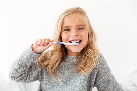 Close-up portrait of female kid brushing her teeth, looking at camera