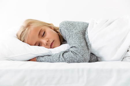 Cute little girl sleeping on white pillow in gray pajamas having pleasant dreams Reklamní fotografie