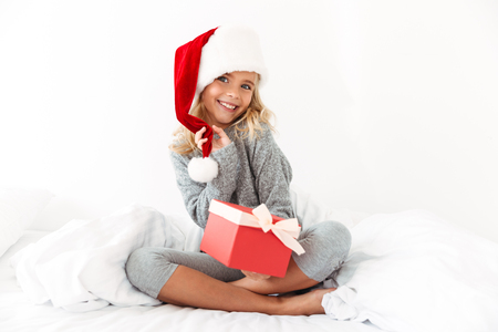 Charming little girl touching her Santas hat holding gift box, looking at camera while sitting on bed