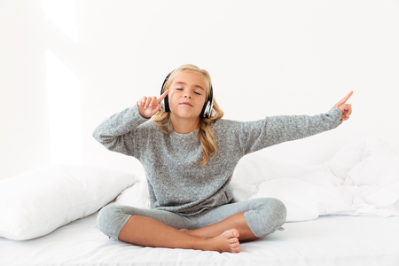 Cute little girl in gray pajamas listening to music with closed eyes while sitting in her bed Фото со стока