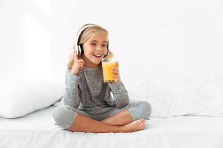 Pretty little blonde girl in gray pajamas holding glass of orange juice, while listening to music in bedroom