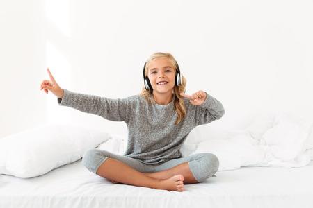 Alegre chica rubia en pijama gris escuchando música y bailando mientras está sentado en su cama, mirando a cámara