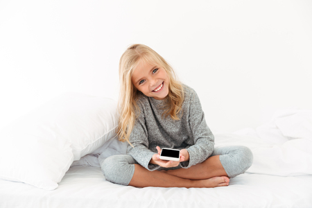 Cheerful girl in gray pajamas holding smartphone, looking at camera while sitting on bed