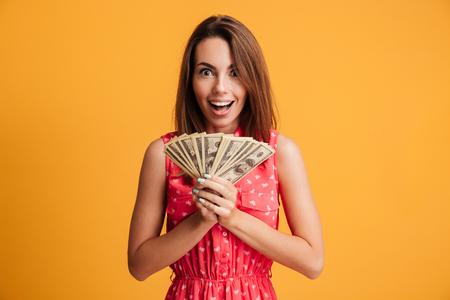 ドル札の束を保持している、黄色の背景に分離カメラ目線の赤いドレスで幸せな若い魅力的な女性
