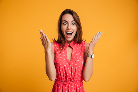 Photo of happy excited amazed young woman in red dress standing with open palms, looking at camera, isolated on yellow background Stock Photo
