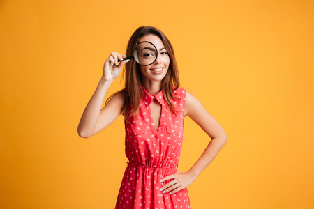 Close-up portrait of cheerful pretty woman in red dress looking at camera through magnifying glass, isolated over yellow background