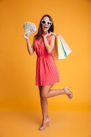 Full-length photo of happy exited young woman in red dress olding credit card and  shopping bags, looking at camera, isolated on yellow background