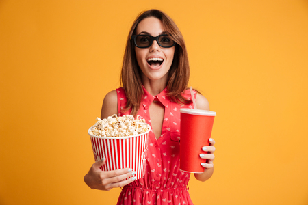 Close-up portrait of happy exited woman in 3d glasses holding cola and popcorn, looking at camera, isolated on yellow background