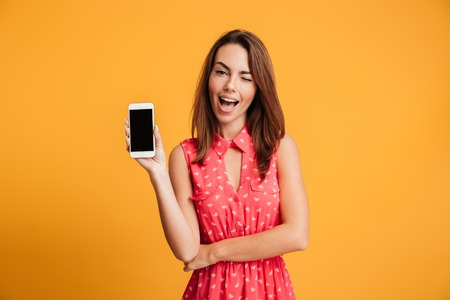 Pleased brunette woman in dress showing blank smartphone screen and looking at the camera over yellow bbackground