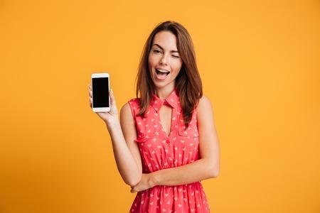 Tevreden donkerbruine vrouw in kleding die het lege smartphonescherm tonen en de camera over gele bbackground bekijken