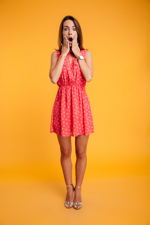 Full length portrait of pretty frightened woman covering her face with hands, looking at camera, isolated on yellow background Stok Fotoğraf - 89401031