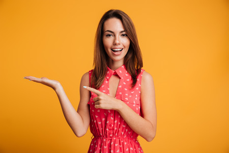 Close-up photo of young pretty woman pointing with finger on her empty palm, looking at camera, isolated on yellow background