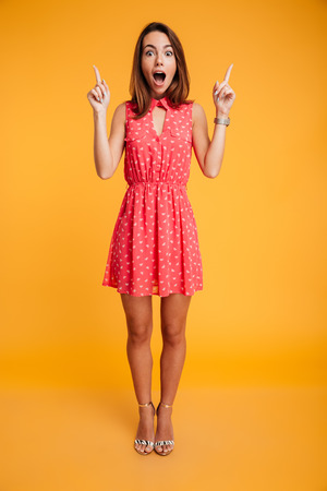 Full length portrait of pretty surprised woman in red dress pointing with two fingers, looking at camera with open mouth, isolated on yellow background