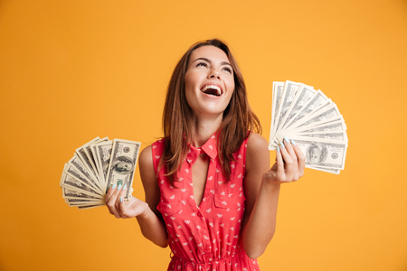 Close-up of young happy woman holding two fans of dollar bills, looking aside, isolated on yellow background