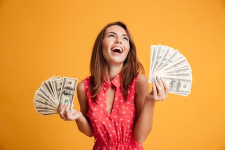 Close-up da jovem mulher feliz segurando dois fãs de notas de dólar, olhando de lado, isolado no fundo amarelo Foto de archivo