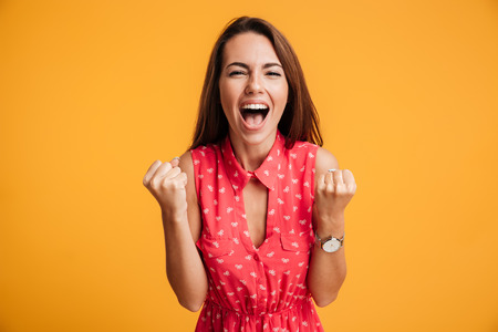 Happy successful young woman with raised hands shouting and celebrating success over yellow background