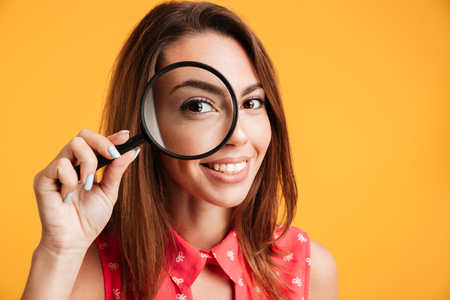 Close up of young cheerful brunette woman looking through magnifying glass, isolated over yellow background