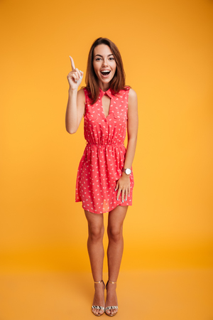 Full length portrait of cute brunette girl in red dress pointing with finger, looking at camera with open mouth, isolated on yellow background