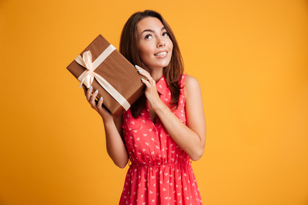 Intrigued runette woman in dress holding gift and looking up over yellow background Stock Photo
