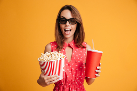 Happy surprised brunette woman in dress and eyeglasses preparing to watch the film while holding popcorn and soda over yellow background Zdjęcie Seryjne
