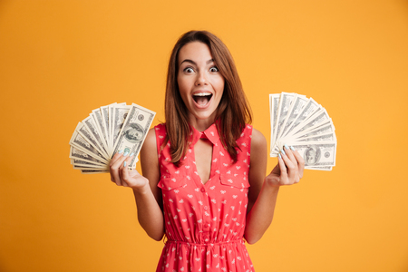 Close-up photo of young happy woman in red dress holding two fans of dollar bills, looking at camera with opened mouth, isolated on yellow background