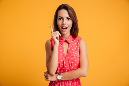 Close-up portrait of charming young woman in red dress pointing with finger, looking at camera, isolated on yellow background Stock fotó