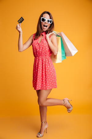 Full-length portrait of young happy woman in sunglasses holding credit card and shopping bags, looking at camera, isolated on yellow background