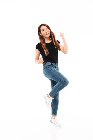 Full length photo of skinny pretty asian woman in casual wear showing winner gesture, looking at camera, isolated on white background Stock Photo