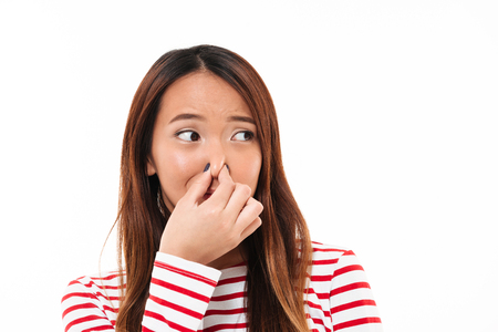 Portrait of a young disgusted asian woman blocking her nose with fingers and looking away isolated over white background