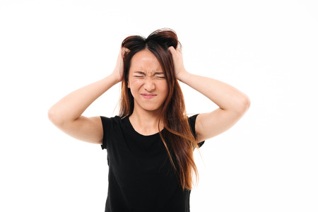 Close-up portrait of annoyed asian woman with closed eyes holding her head, isolated over white background Stock Photo