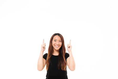 Young cheerful asian girl in black tshirt  pointing with two fingers upward, looking at camera, isolated over white background