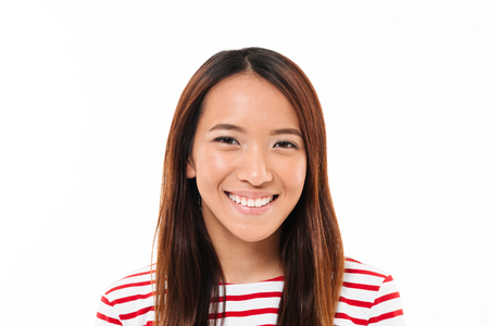Close up portrait of a cheerful young asian girl looking at camera isolated over white background