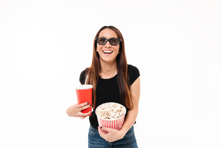 Portrait of a laughing asin girl in 3d glasses holding popcorn box and looking at camera isolated over white background 스톡 콘텐츠