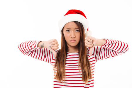 disapprove: Portrait of a sad asian girl in christmas hat standing and showing thumbs down isolated over white background