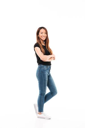 Zijaanzicht van jonge mooie Chinese vrouw in zwarte t-shirt en jeans die zich met gekruiste handen bevinden, bekijkend camera, die over witte achtergrond wordt geïsoleerd