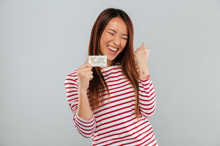 Heureuse femme asiatique en pull se réjouir et détenant la carte de crédit sur fond gris Banque d'images