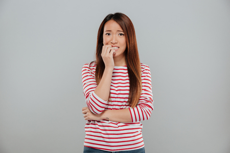 Portrait of a nervous asian girl biting her nails while looking at camera isolated over gray background