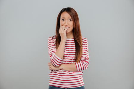 灰色の背景の上に孤立したカメラを見ながら、彼女の爪をかむ神経質なアジアの女の子の肖像