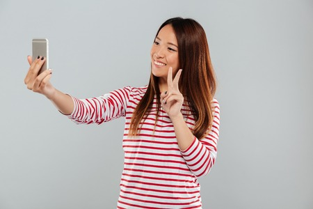 Photo of cheerful young asian woman make selfie by phone standing isolated over grey wall. Looking aside showing peace gesture.