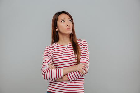 Retrato, de, um, deprimido, mulher asian, ficar, com, braços dobraram, e, olhando, cópia espaço, isolado, sobre, experiência cinza Foto de archivo - 89401111