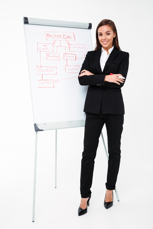 Image of happy pretty businesswoman isolated over white background near business plan and showing it. Looking camera.