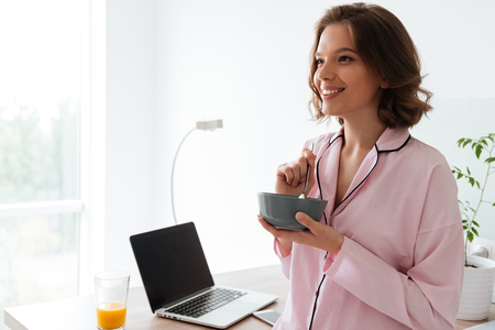 comfort food: Portrait of a pretty young girl in pajamas having a breakfast at the kitchen with blank screen laptop computer on a table Stock Photo
