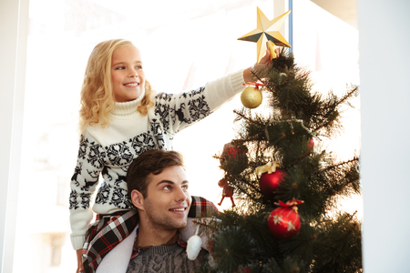 Young man with his daughter on his shoulders helping her decorate the Christmas tree