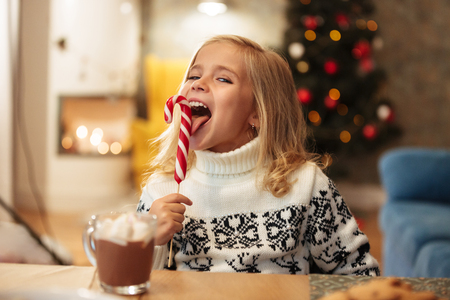 Close-up photo of funny little girl licks candy cane, looking at camera