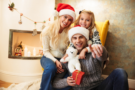 Young smiling father in Santas hat pointing with finger on you, holding gift box while sitting with his family at fireplace
