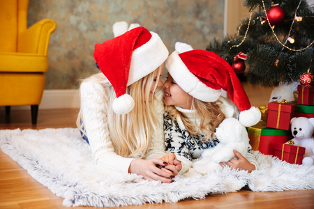 Young mother in Santa's hat and her little daughter touching each other's with noses while luing on white carpet in living room Archivio Fotografico
