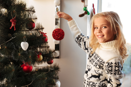 Close-up portrait of pretty little girl holding red ball, looking at camera at Chrismas tree